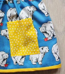 O. Carol détail d'une jupe bleue à motifs ours blanc avec bords et poches jaunes
